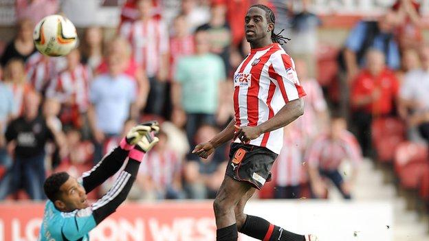 Clayton Donaldson chips Swindon keeper Wes Foderingham for Brentford's third goal at Griffin Park