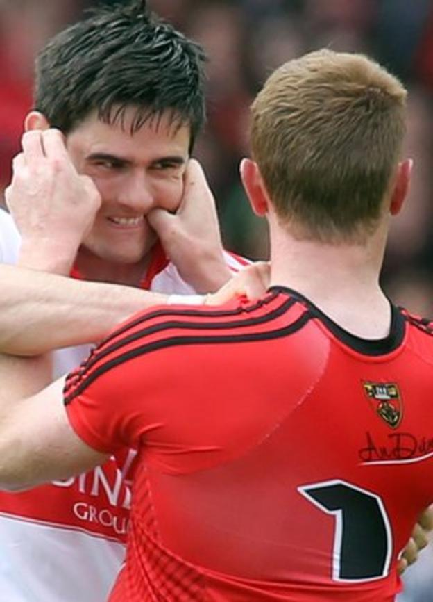 Derry defender Chrissy McKaigue clashes with Down forward Benny Coulter