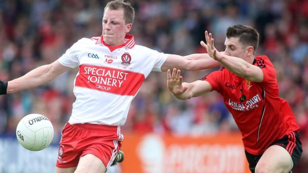 Derry's Brian McCallion attempts to get his kick away before Ryan Boyle comes in with a block