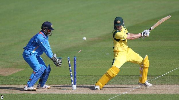 Australia batsman Adam Voges (right) is bowled as India's MS Dhoni looks on