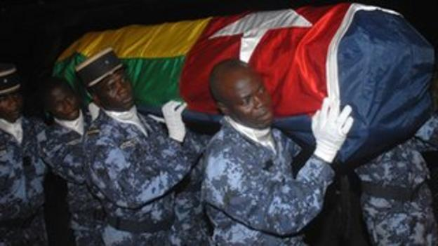 Togolese police carry the coffin of one of the victims of the 2010 Cabinda attack upon its return to Lome airport.