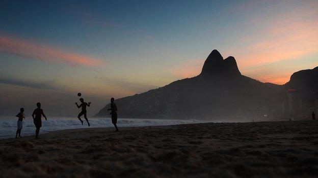 Brazilians play football on a beach in Rio de Janeiro