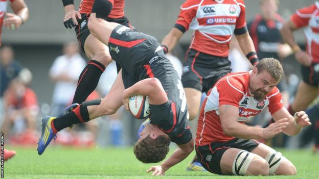 Wales wing Harry Robinson is tackled by Michael Broadhurst, the Japan flanker who scored one of the home side's two tries in Tokyo