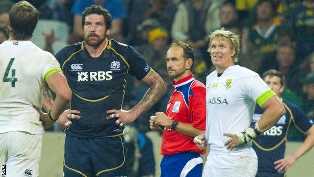 Referee Roman Poite (centre) awaits a replay of an incident involving Jim Hamilton (left) before showing the Scotland lock a yellow card