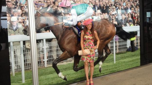 First-time racegoer Hannah King poses in front of a photo of Frankel