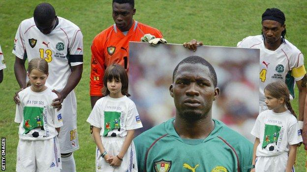 Cameroon players hold a picture of Marc-Vivien Foe