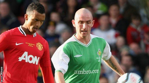 Barry Johnston closes down Manchester Utd's Nani while playing for an Irish League XI