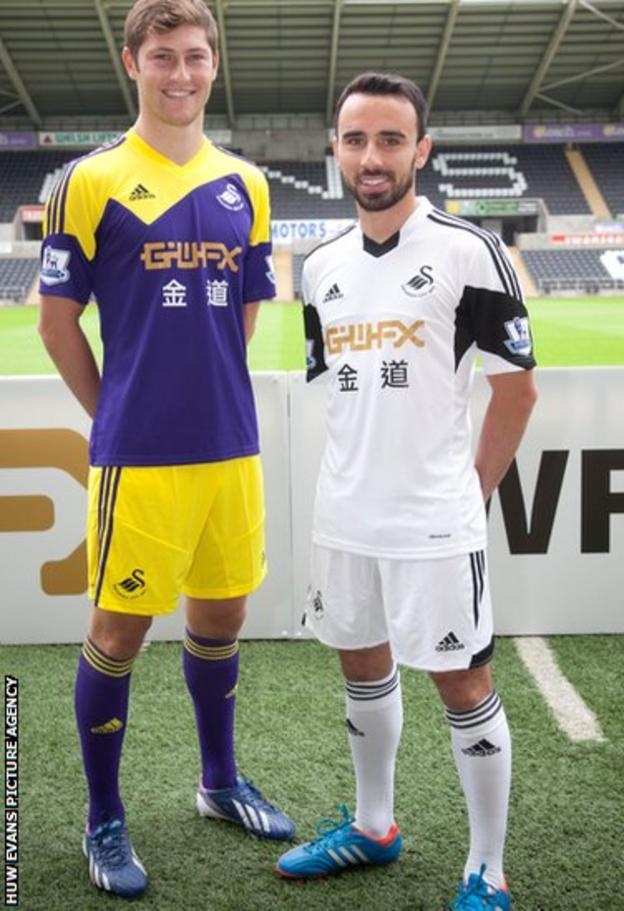 Swansea City players Ben Davies and Leon Britton sport the club's new home and away shirts at the Liberty Stadium.