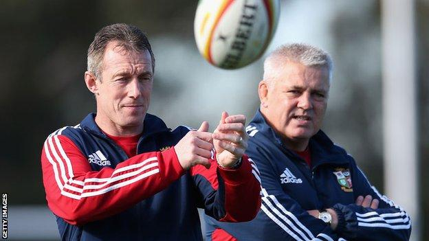 Rob Howley passes the ball during a Lions training session with Warren Gatland looking on