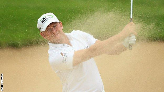 Jamie Donaldson sends the sand flying as he plays out of a bunker