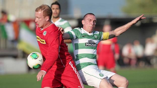Cliftonville's Liam Boyce and Celtic's Scott Brown battle for possession during the first half at Solitude