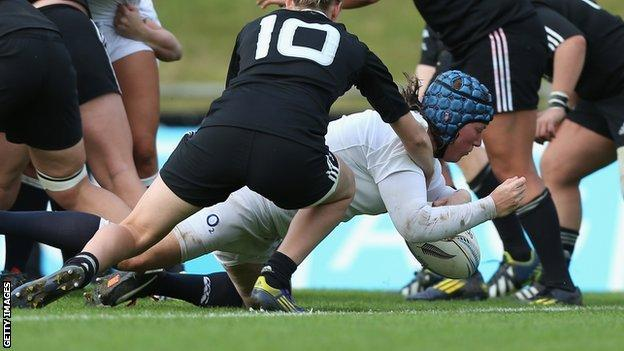 Rochelle Clark (in white) scores a try for England