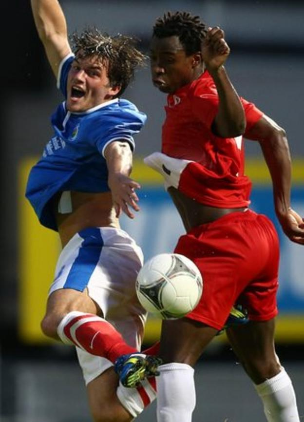 Linfield midfielder Philip Lowry competes against FC Xanthi defender Paito