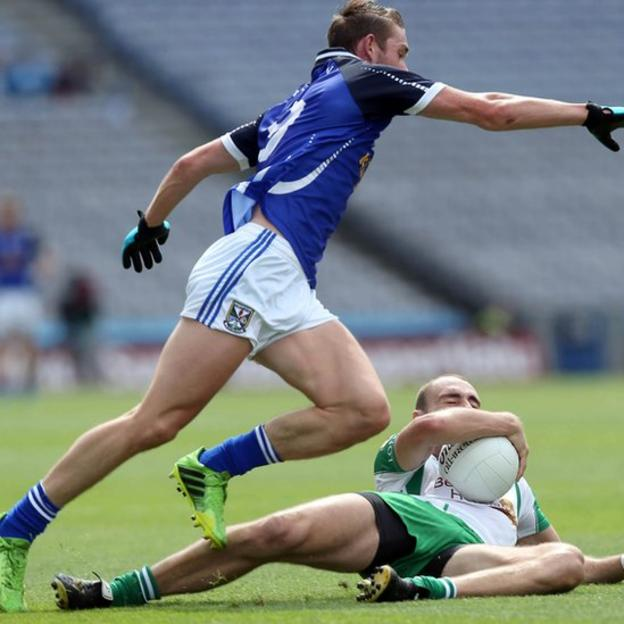 Cavan midfielder David Givney moves in as Caolan Doyle of London clings to the ball on the ground of Croke Park