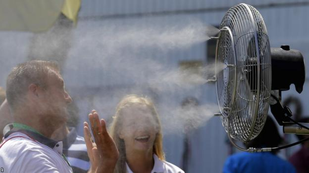 Man cooling himself in front of a fan