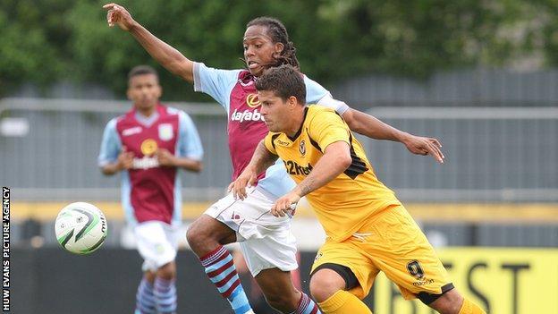 Newport's Danny Crow battles for the ball with Villa's Daniel Johnson