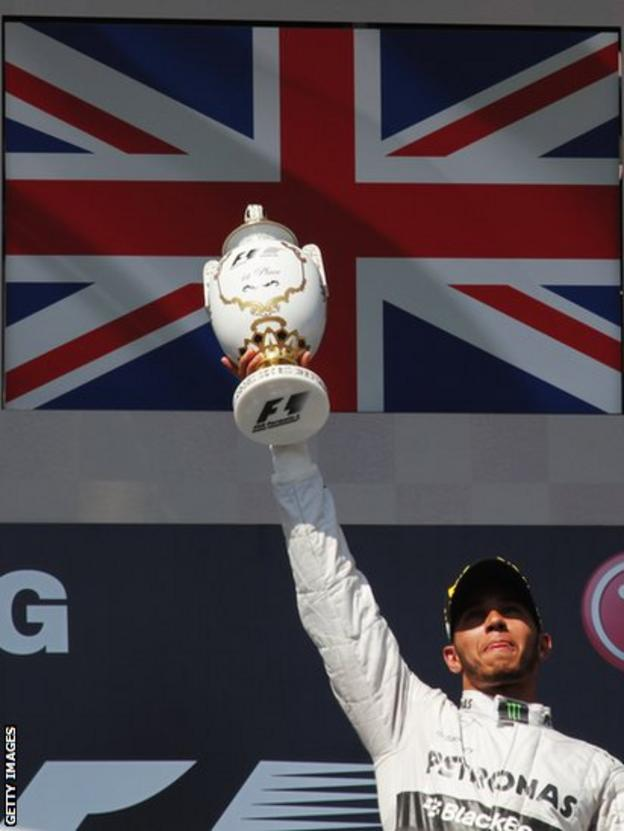 Lewis Hamilton lifts the winners' trophy