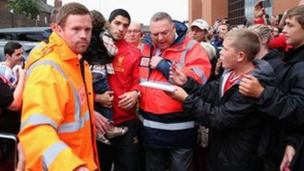 Liverpool striker Luis Suarez is mobbed by the club's fans at Anfield