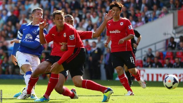 Ross Barkley (L) of Everton shoots past Ben Turner and Steven Caulker of Cardiff City