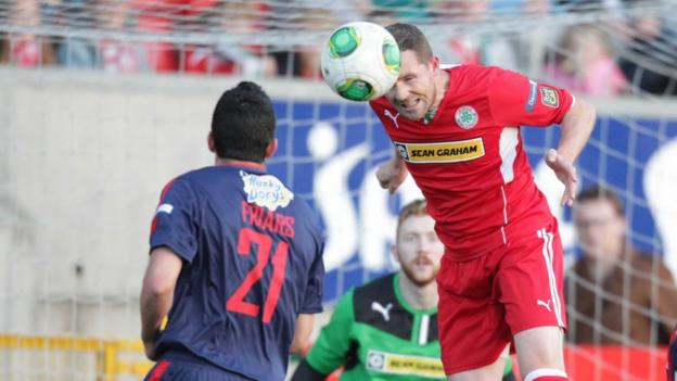 Cliftonville's Marc Smyth heads the ball as Portadown defender Emmett Friars looks on