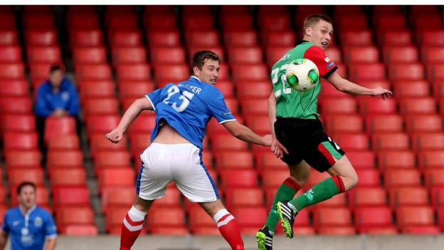 Mark McAllister and Calum Birney take to the air during Saturday's Belfast derby at Windsor Park