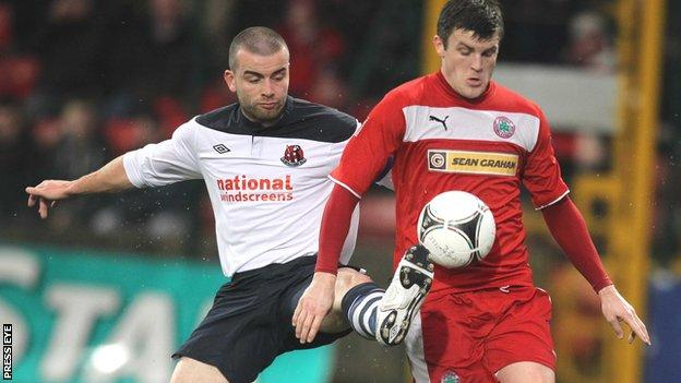 Colin Coates gets his toe to the ball ahead of Cliftonville's Diarmuid O'Carroll
