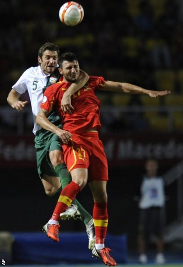 """Sam Ricketts, winning his 50th Wales cap, jumps for the ball with Macedonia""""s Jovan Kostovski during the World Cup Qualifier in Skopje."""