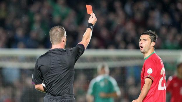 Referee Danny Makkelie shows Helder Postiga a red card for a head-butt on Gareth McAuley late in the first half