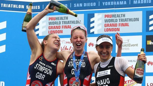 World champion Non Stanford is doused with Champagne by fellow British athlete Jodie Stimpson who finished second in the series. Third-placed Anna Haug joins in the celebrations.