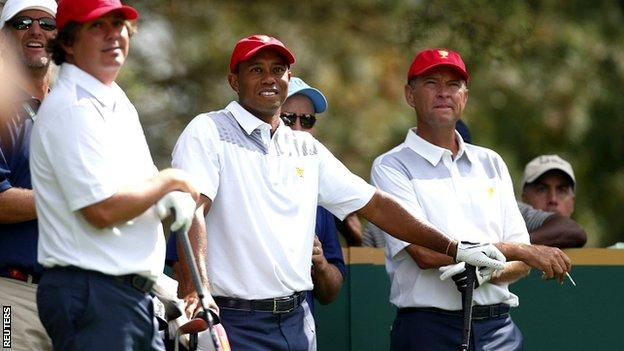 US team members Jason Dufner (L) and Tiger Woods and assistant captain Davis Love III
