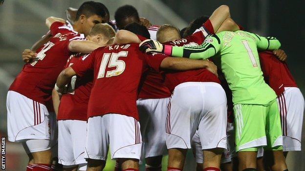 Swindon players huddle before the League Cup clash with Chelsea