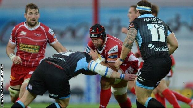 George Earle of the Scarlets runs into a Glasgow tackler