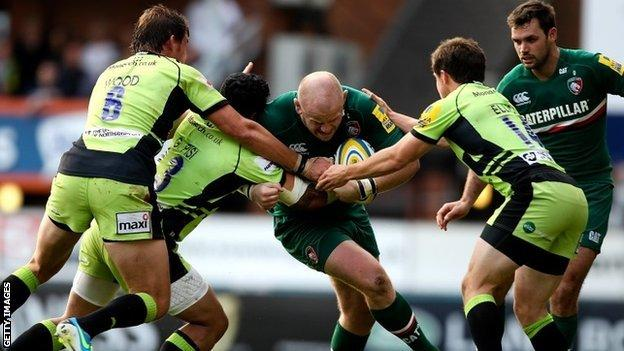 Leicester's Dan Cole is tackled by three Northampton players