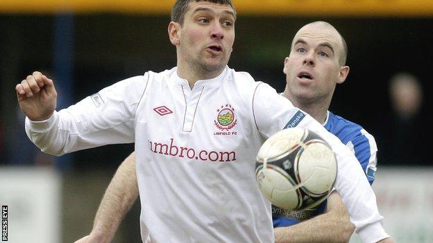 Linfield's Matthew Tipton shields the ball from Dungannon defender Adam McMinn