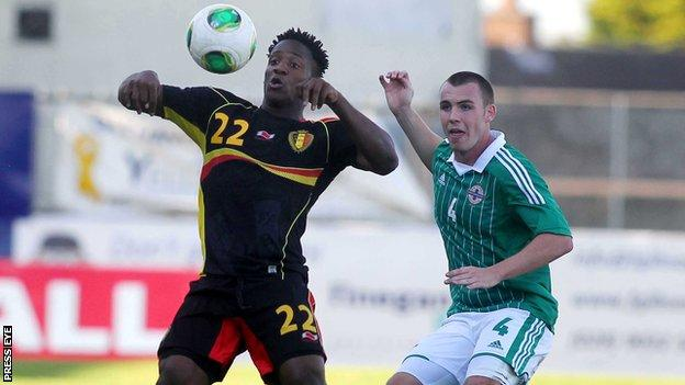Northern Ireland's Luke McCullough is about to challenge Belgian goalscorer Michy Batshuayi