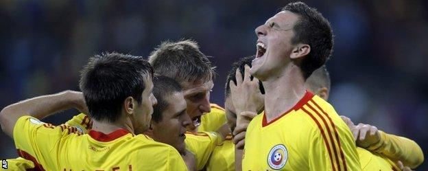Romania celebrate their crucial second goal against Estonia