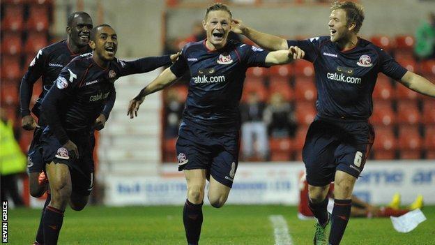 Craig Westcarr, Ashley Hemmings and Nicky Featherstone help celebrate Walsall midfielder Sam Mantom's goal at Swindon