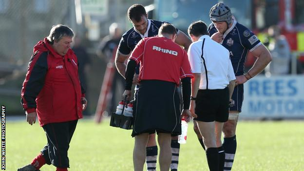 Players and officials look at the hole in the pitch during Aberavon v Bristol