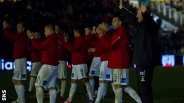 Inverness boss Terry Butcher and his players salute their travelling fans in darkness