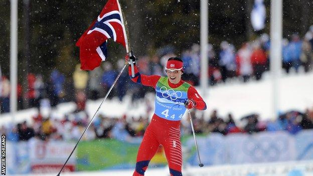 Marit Bjoergen celebrates after winning one of a record five medals at the Vancouver Olympics