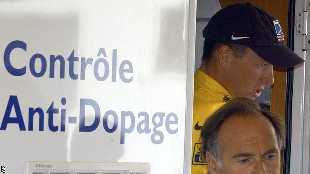 Lance Armstrong walks out of the Tour de France's anti-doping control bus