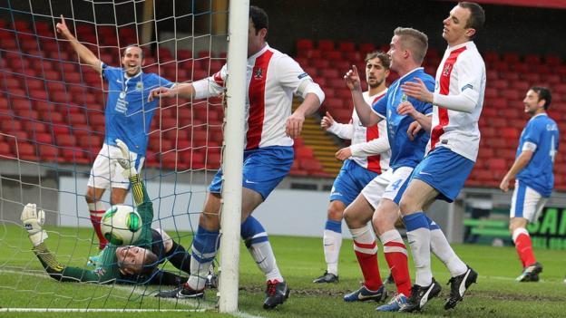 Linfield celebrate after Niall Quinn's free-kick beats Ards goalkeeper Graeme McKibbin during the Premiership match at Windsor Park