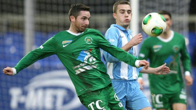 Jason McCarthy of Ballinamallard battles for possession against Warrenpoint Town opponent Ruairi Devlin