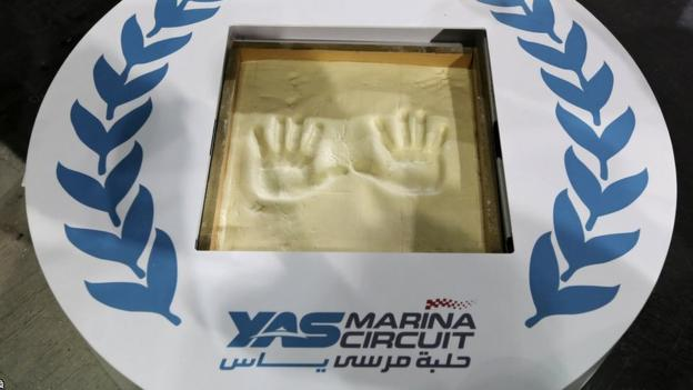 Sebastian Vettel's handprints are displayed in a Yas Marina Circuit logo