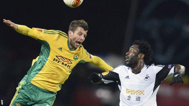 Kuban defender Angel Dealbert (L) jumps for the ball with Swansea forward Wilfried Bony
