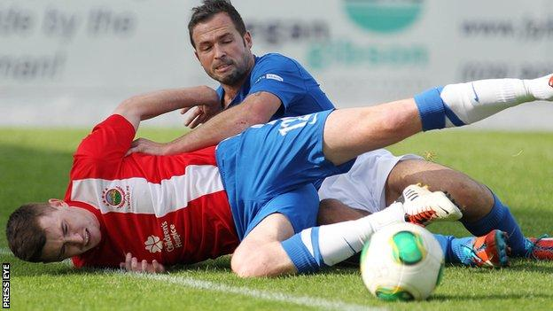 Crusaders striker David Rainey in action against Billy Joe Burns of Linfield