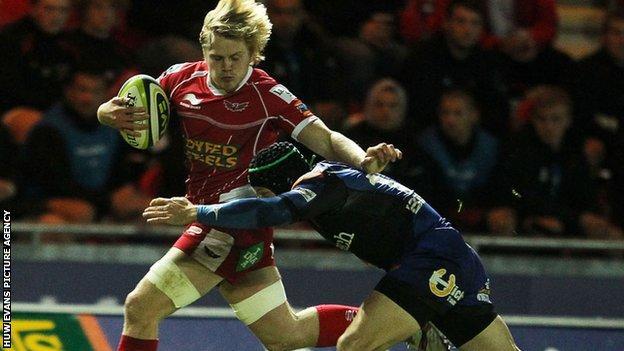 Scarlets' Daniel Thomas is tackled by Dragons fly-half Kris Burton