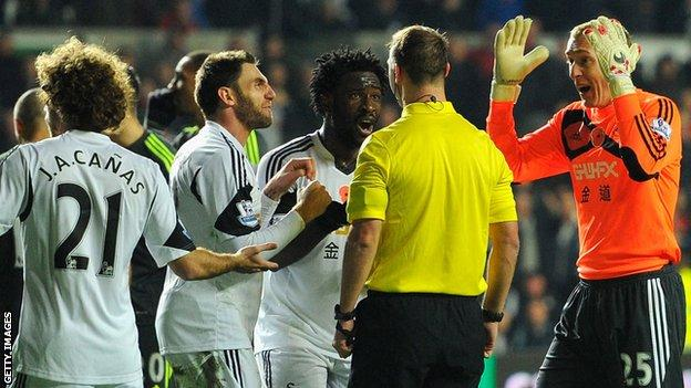 Angel Rangel and other Swansea players remonstrate with referee Robert Madley after he awarded a penalty to Stoke
