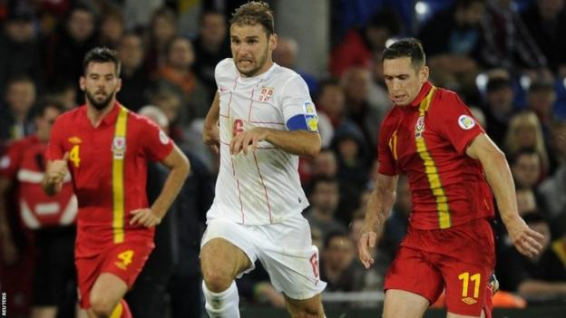Wales' Andrew Crofts (right) fails to challenge Serbia's Branislav Ivanovic during their 2014 World Cup qualifying match at Cardiff City Stadium