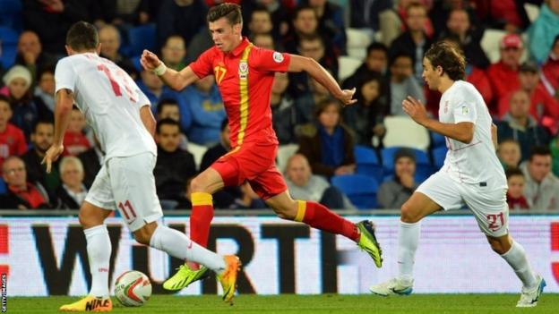 Wales' Gareth Bale (centre) runs with the ball against Serbia's Aleksandar Kolarov (left) and Lazar Markovic (right)
